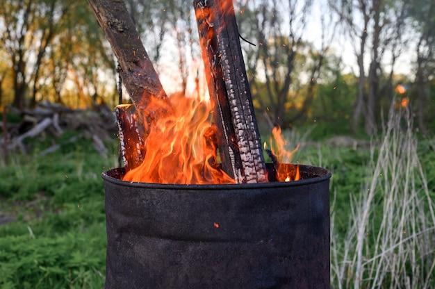 Spalanie śmieci w zardzewiałej metalowej beczce