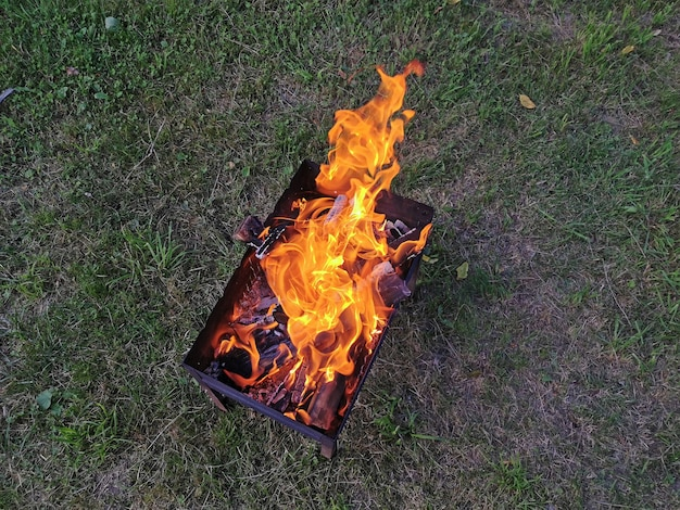 Spalanie węgli drewna w zbliżeniu grilla. zielone tło z tyłu. widok z góry