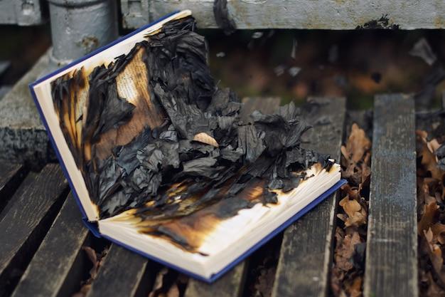 Spalona książka i strony na drewnie i liściach