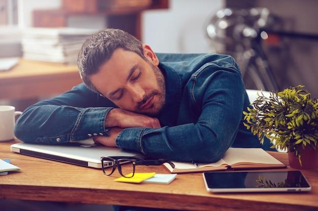 Spanie w miejscu pracy. młody mężczyzna opiera głowę o biurko i ma zamknięte oczy, siedząc w swoim miejscu pracy