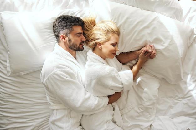 Spanie w objęciach i intymności kochającego partnera z delikatnymi dotknięciami w łóżku. piękna para w luksusowym hotelu napełnia się pozytywną energią. romantyczny śpiący śliczny ptaszek, trzymający się za ręce, przytulający