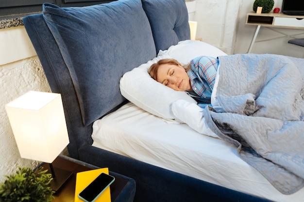 Spanie w sypialni. spokojna dojrzała kobieta leżąca na łóżku przykryta i ciepła, mająca smartfon na stoliku nocnym
