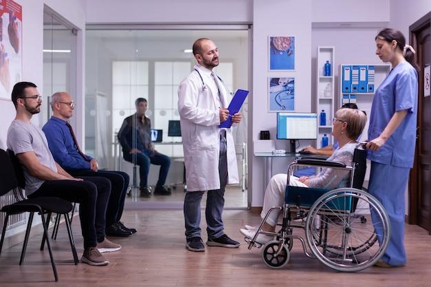Sparaliżowana niepełnosprawna starsza kobieta na wózku inwalidzkim odwiedza lekarza specjalisty w celu kontroli okresu