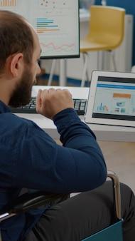 Sparaliżowany menedżer używający komputera i tabletu w tym samym czasie