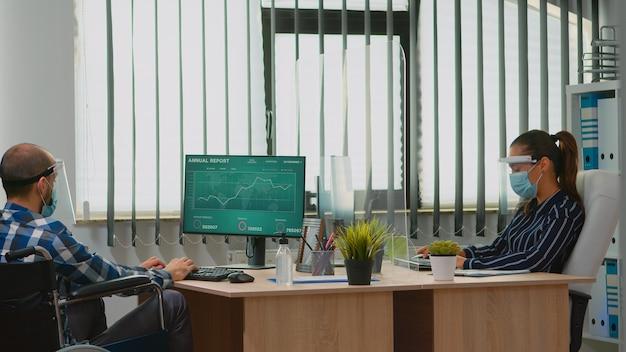 Sparaliżowany pracownik finansowy jadący na wózku inwalidzkim w nowym normalnym biurze firmy z maską ochronną macha na kolegę. unieruchomiony freelancer w firmie szanującej dystans społeczny.