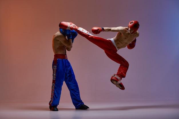 Sparing bokserów płci męskiej. skaczący zawodnik, kopiąc w nokaut, zawodnik sztuk walki