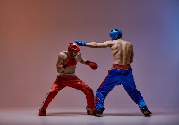 Sparing dwóch samców walczących w rękawicach bokserskich podczas walki, sztuk walki, treningu walki mieszanej
