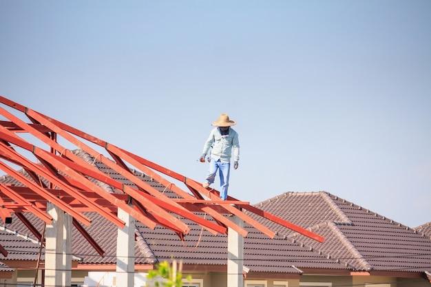 Spawacz budowlany montuje konstrukcję szkieletową dachu domu na budowie z chmurami i niebem