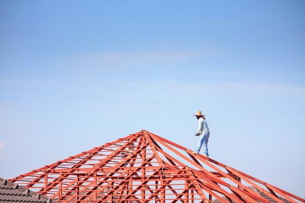 Spawacz budowlany pracowników instalujących stalową konstrukcję szkieletową dachu domu na budowie z chmurami i niebem