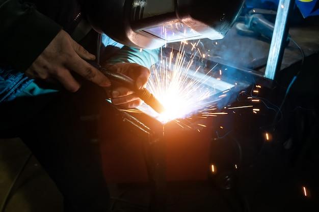 Spawacz gotuje ramę. spawacz gotuje metal. spawacz gotuje konstrukcje metalowe. prace spawalnicze. iskry, stopiony metal