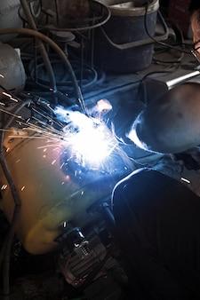 Spawacz pracuje spawalniczego metalu i iskier