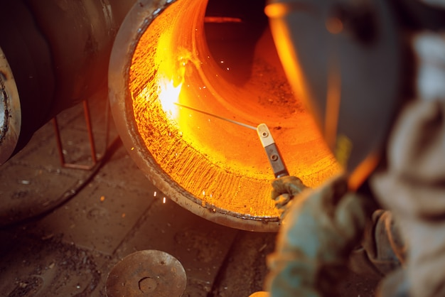 Spawacz pracuje z metalem w fabryce, umiejętności spawalnicze