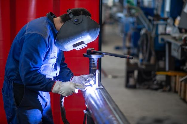Spawacz przy pracy w zakładzie produkcyjnym, człowiek spawający rurę żelazną lub stalową