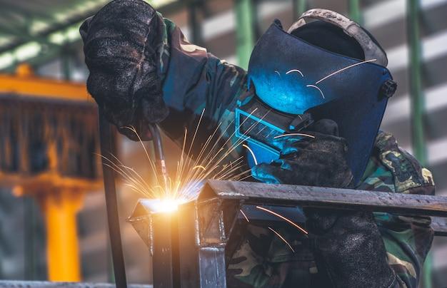 Spawacz spawa metalową część w fabryce samochodów