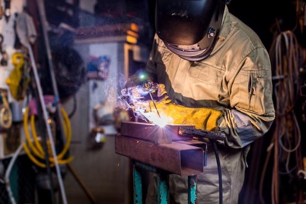 Spawacz spawa metalową część w fabryce. spawacz w mundurze ochronnym i masce do spawania metalowych rur w przemyśle