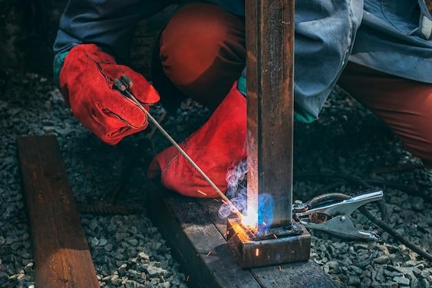 Spawacz spawa metalowy słup spawaniem elektrycznym, trzyma w rękach elektrodę
