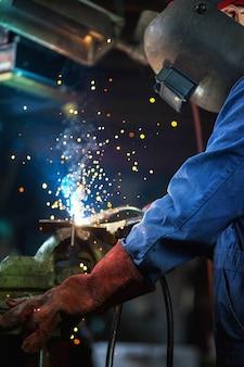 Spawacz spawa w garażu, pracownik przemysłowy robotnik w fabryce spawania konstrukcji stalowych