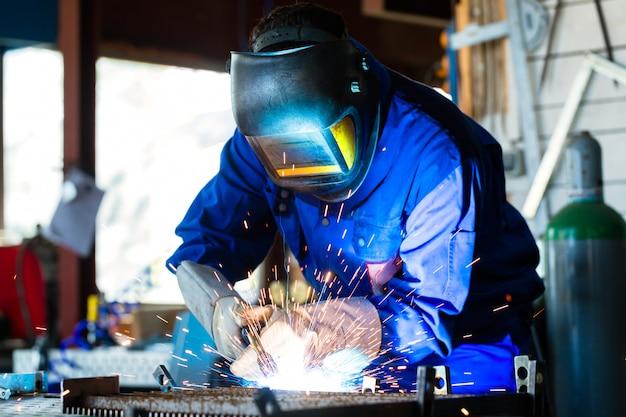 Spawacz spawalniczy metal w warsztacie z iskrami