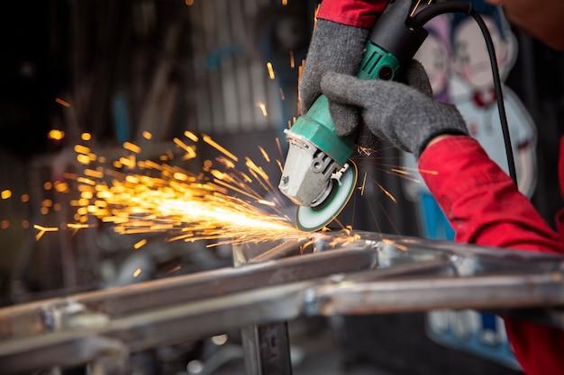 Spawacz używał kamienia szlifierskiego na stali w fabryce z iskrami, proces spawania w warsztacie przemysłowym, ręce z instrumentem w ramie.