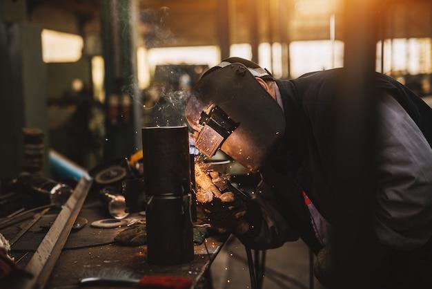 Spawacz w mundurze ochronnym i masce zgrzewający metalową rurę na stole przemysłowym podczas iskier.