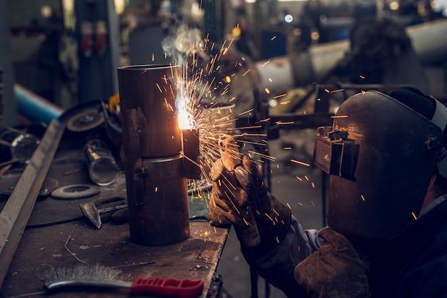 Spawacz w mundurze ochronnym i masce zgrzewający metalową rurę na stole przemysłowym z innymi narzędziami podczas lotu iskier.