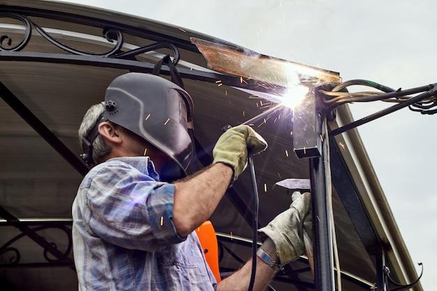 Spawacz z maską ochronną do spawania metalu wykonuje prace spawalnicze