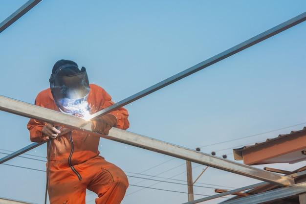 Spawanie robocze w pomarańczowym spawaniu odzieży roboczej wiązanie dachowe