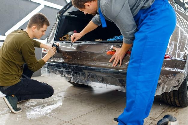Specjaliści nakładają folię ochronną na samochód na tylny zderzak.