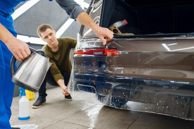 Specjaliści nakładają folię ochronną na tylny zderzak. montaż powłoki chroniącej lakier samochodu przed zarysowaniami. nowy pojazd w garażu, procedura tuningu