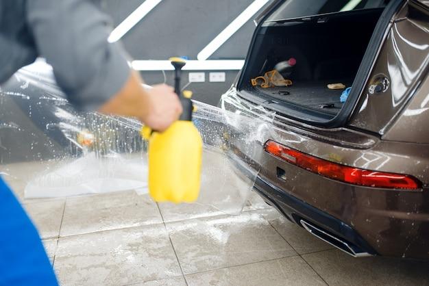 Specjaliści nakładają folię ochronną na tylny zderzak. montaż powłoki chroniącej lakier samochodu przed zarysowaniami. nowy pojazd w garażu, tuning