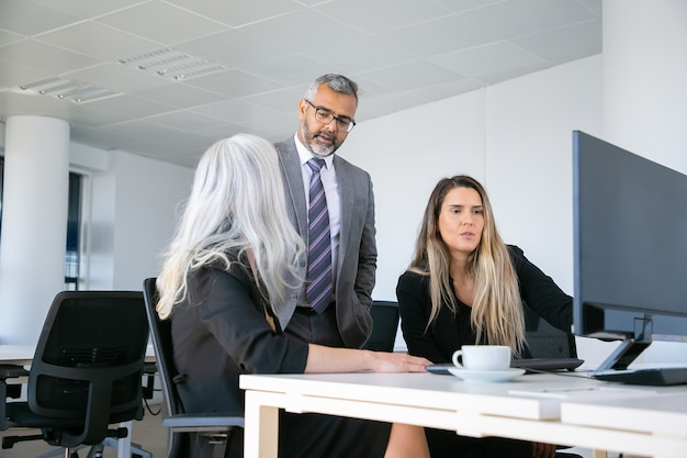 Specjaliści omawiają projekt z szefem w miejscu pracy, oglądają prezentację na monitorze komputera. koncepcja komunikacji biznesowej
