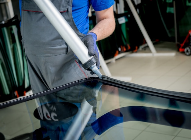 Specjaliści samochodowi zastępujący przednią szybę lub przednią szybę samochodu w garażu stacji obsługi samochodowej.