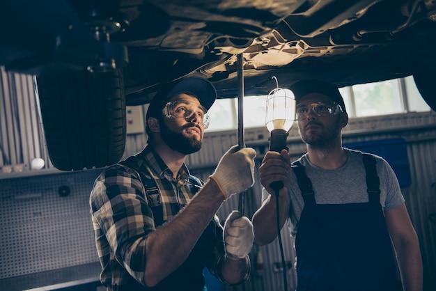 Specjaliści w niebieskim kombinezonie badający samochód