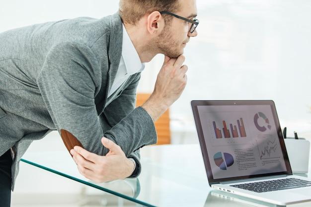 Specjalista ds. finansów spogląda na ekran laptopa z wykresami finansowymi rozwoju firmy.