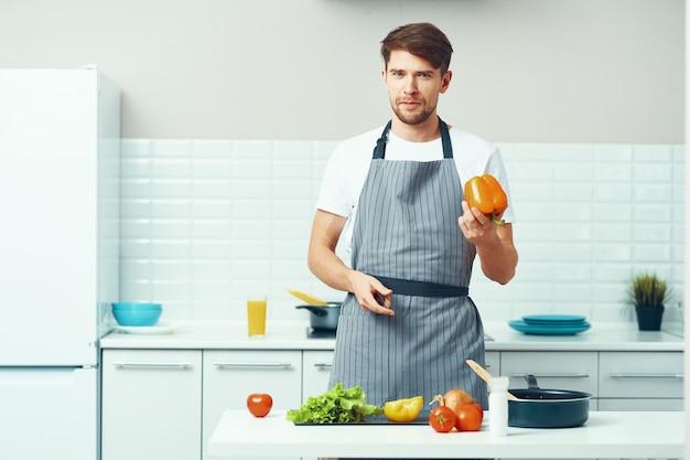 Specjalista kucharz mężczyzna w szarych fartuchach i świeżych warzywach na stole