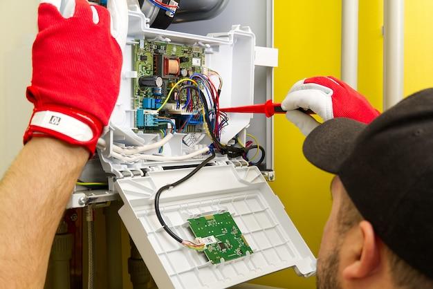Specjalista naprawia elektronikę kotła gazowego w prywatnym domu
