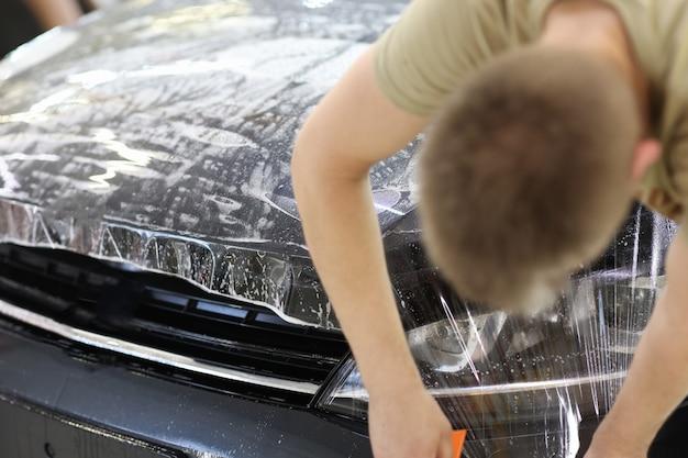 Specjalista od oklejania samochodów nakładający folię lub folię winylową na samochód ochronny nakładający folię ochronną