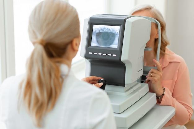 Specjalista okulista wykorzystujący technologie komputerowe podczas badań przesiewowych