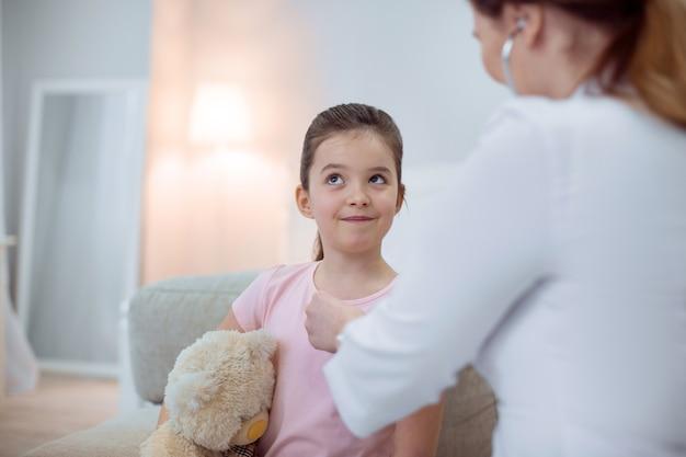 Specjalista pediatra. cieszę się, że zamyślona dziewczyna szuka i przytulanie pluszowego misia, podczas gdy kobieta lekarz za pomocą stetoskopu