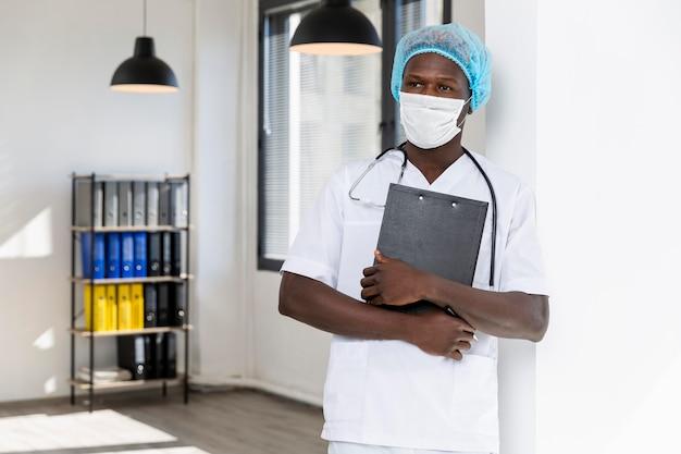 Specjalista samiec lekarka trzyma czarnego schowek