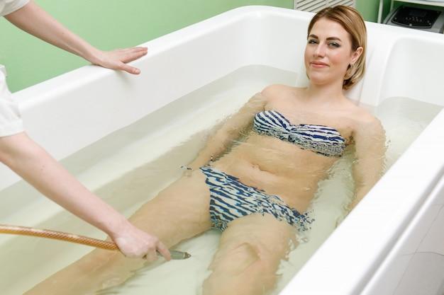 Specjalista stosuje hydroterapię w kąpieli. podwodny hydromasaż w salonie kosmetycznym