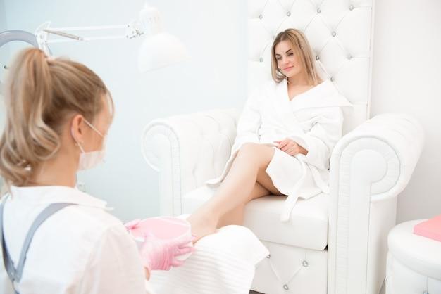 Specjalista w gabinecie kosmetycznym w maseczce i różowych rękawiczkach ochronnych wykonujący pedicure dla klientki