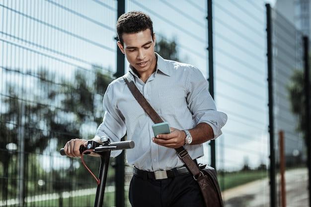 Specjalna aplikacja. uważny, spokojny facet uruchamia aplikację do jazdy na skuterze elektrycznym