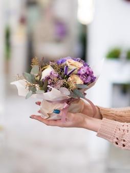 Specjalna dostawa bukietu kwiatów dla bliskiej ci osoby. kobiece ręce trzymające kreatywny układ kwiatowy