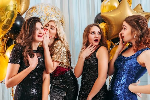 Specjalna okazja. pani szepcząca do ucha przyjaciółce intrygujące, zaskakujące wieści. ostrożne młode kobiety.
