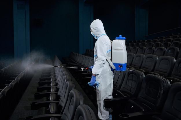 Specjalna osoba wykonująca dezynfekcję w sali kinowej.