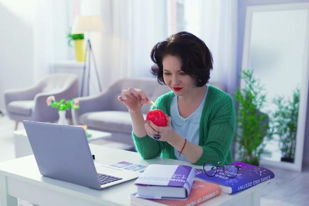 Specjalna świeca. miła miła kobieta trzyma czerwoną świecę siedząc w swoim miejscu pracy