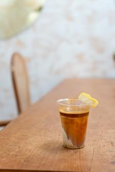 """Specjalne menu kawowe o nazwie """"brudna kawa"""". na dole zimne mleko z gorącym espresso na wierzchu z cytryną"""