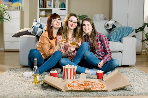 Specjalne wydarzenie. usługa szybkiej dostawy jedzenia. trzy młode panie w zwykłych strojach jedzą pyszną pizzę, popcorn i piją wino na ich fantazyjnej imprezie.