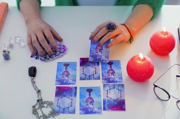 Specjalne znaczenie. widok z góry karty tarota znajdującej się w rękach wróżek podczas sesji